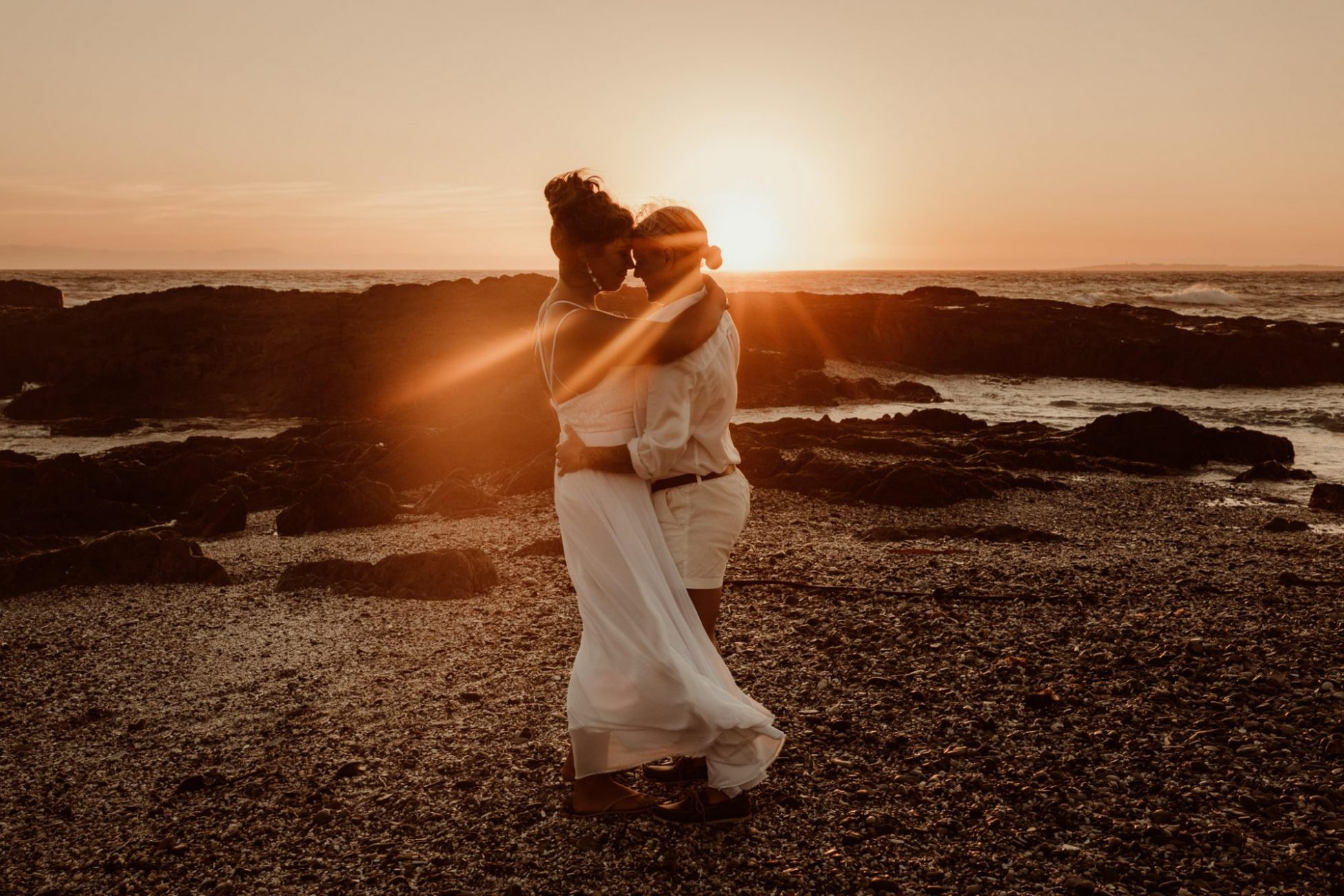 sunset sunrays coming through a couple of brides hugging