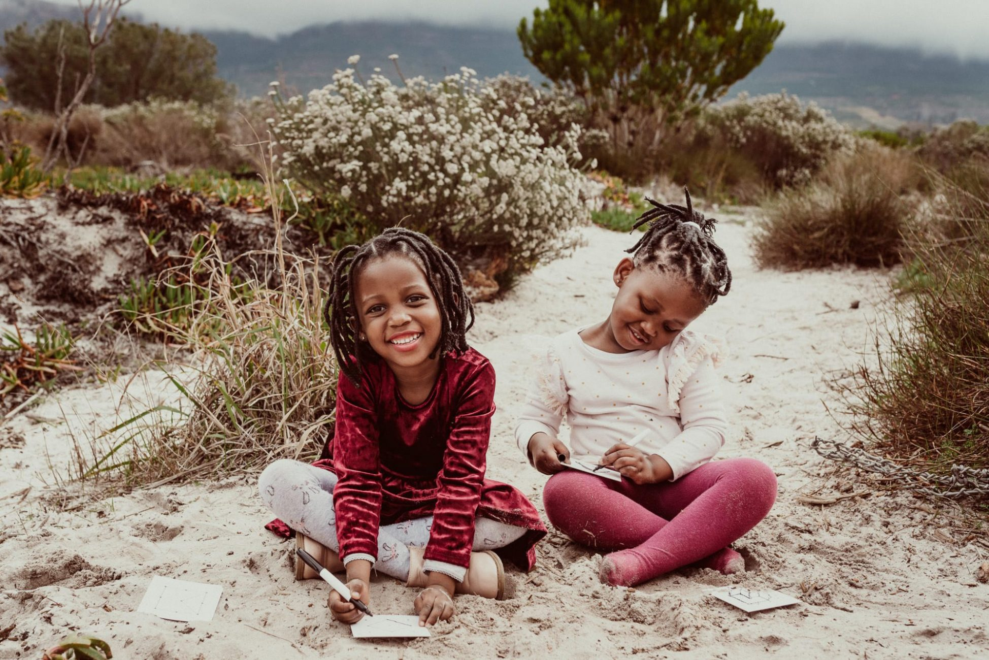 tokai-forest-family-photoshoot-two-daughters-nature-smile-sisters-capetown-photographer-moody-weather-sitting-in-sand