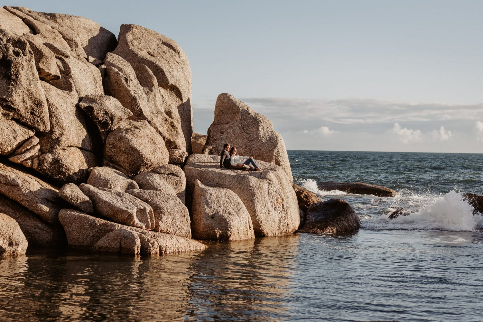 maidens_cove_ocean_boulders_sunset_golden_hour-cr8tive-duo-couple-session_sitting _on_rock