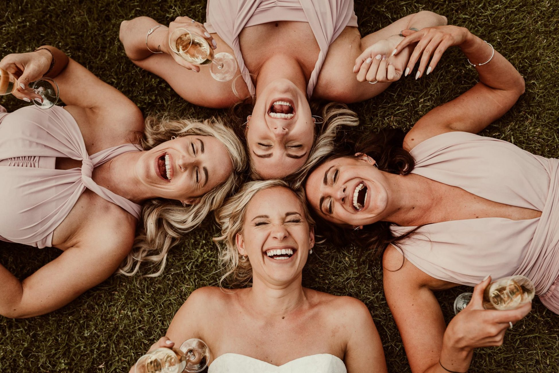 paarl_rhebokskloof_cr8tiveduo_capetown_photographer_wedding_bride_bridesmaid_creative_photoshoot_laugh_champagne_glasses_lying_on_grass